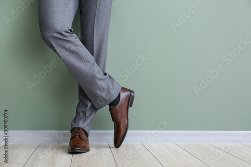 Obraz Young man in stylish shoes near color wall - fototapety do salonu