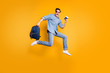 Full length body size turned photo of screaming man running jumping towards airport in white shoes and satchel in hands isolated vivid yellow color background