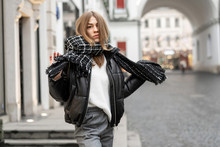 Closeup Portrait Of A Caucasian Young Model In An Oversized Warm Leather Jacket And Knitted Scarf On Street Near A Glass Shop Window. Life Style