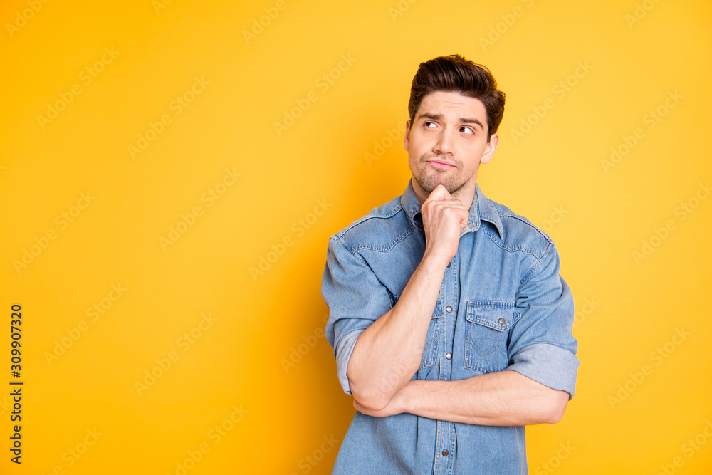 Fototapeta Photo of pensive interested man looking into empty space contemplating new creative ideas touching his skin isolated vibrant color background