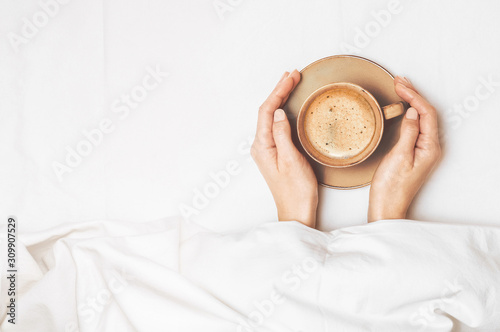 Fotografie, Obraz Female hands are holding a cup of morning coffee on the background of a white bedsheet under the covers in bed