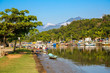 Idyllic view of river Perequê-Açu at lowe tide with colorful tour boats, trees and rainforest mountains on a sunny day in Unesco World Heritage town Paraty, Brazil