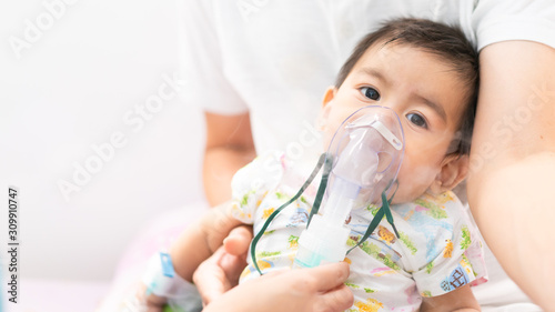 Photo Close up of asian little baby boy is treated respiratory problem with vapor nebulizer to relief cough symptom in the hospital room , concept of pediatric patient care for sick in the hospital