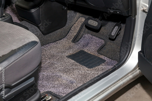 Photo Dirty car floor mats of gray carpet with gas pedals and brakes in the workshop for the detailing vehicle before dry cleaning