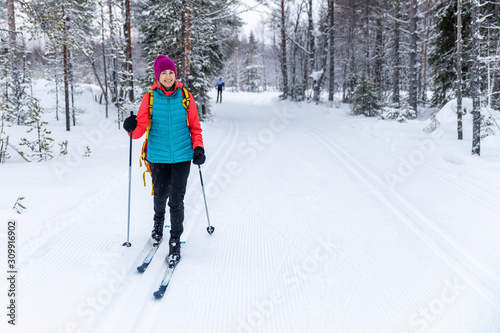 Fototapeta cross country skiing - woman with skis on snowy forest ski track