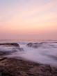 Morning wave coming through between rocks.