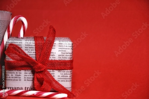 Fotografía Gifts wrapped in old newspaper on red background