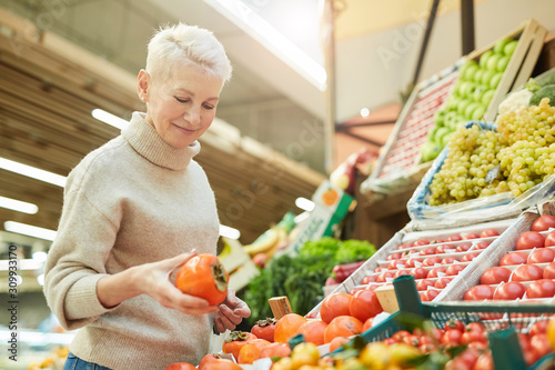 Waist up portrait of beautiful adult woman choosing fresh vegetables while grocery shopping at farmers market, copy space