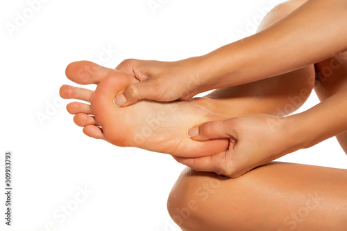 Cuadros en Lienzo  woman massaging her painful foot on white background