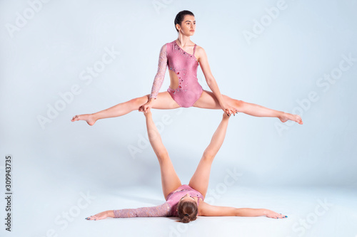 Two flexible girls gymnasts with pigtails, in pink leotards are performing splits using support while posing isolated on white background. Close-up.