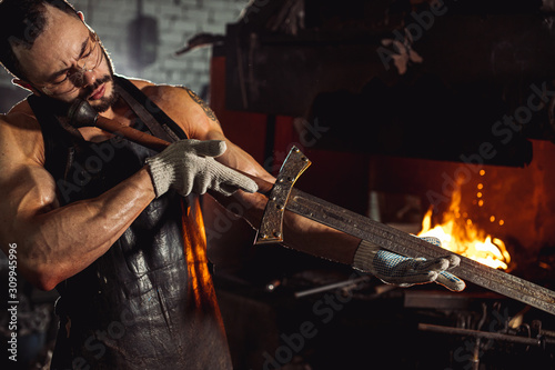 Fotografia, Obraz portrait of muscular strong forger studying handmade metal in workshop near furn