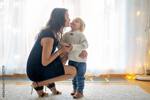 Young mother, fashionly dressed, hugging and kissing her toddler boy Obraz na płótnie