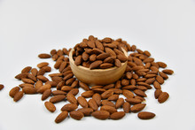 Roasted Almonds In Wooden Bowl On White Background. Close Up Photo Of Roasted Almonds.
