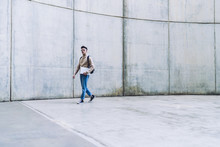 Young Male In Glasses Carrying Laptop Near Concrete Wall