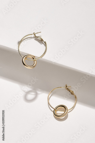 Subject shot of a pair of hoop earrings isolated on the white geometric design surface Fototapet
