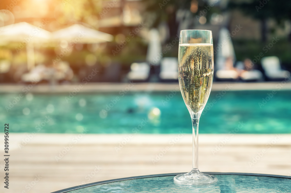 Fototapeta Close-up white champagne or prosecco glass against poolside at luxury resort hotel during vacation. Sparkling wine with rising bubbles with blue pool background outdoor. Refreshing alcohol drink