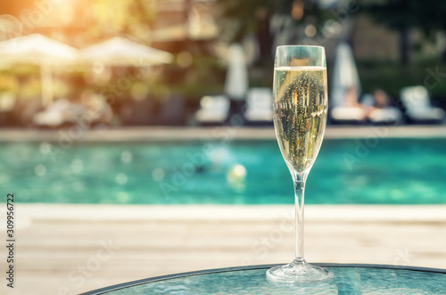 Fotografía Close-up white champagne or prosecco glass against poolside at luxury resort hotel during vacation