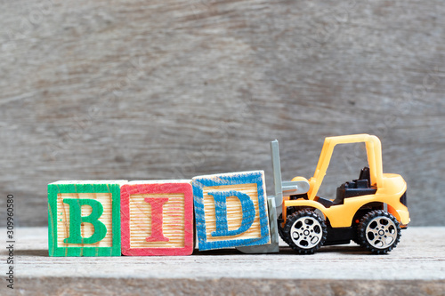 Toy forklift hold letter block d to complete word bid on wood background Canvas Print