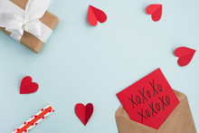 Valentines Day Concept. Gift Box, Red Hearts And Envelope With Card On Light Blue Background. Minimal Composition. Top View, Flat Lay, Copy Space