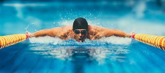 Man in swimming pool. Butterfly style. Matte effect