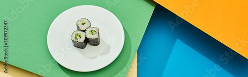Fototapeta fresh maki with cucumber on plate on multicolored surface, panoramic shot obraz