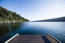 Wooden Dock Extends Over Placid Mountain Lake