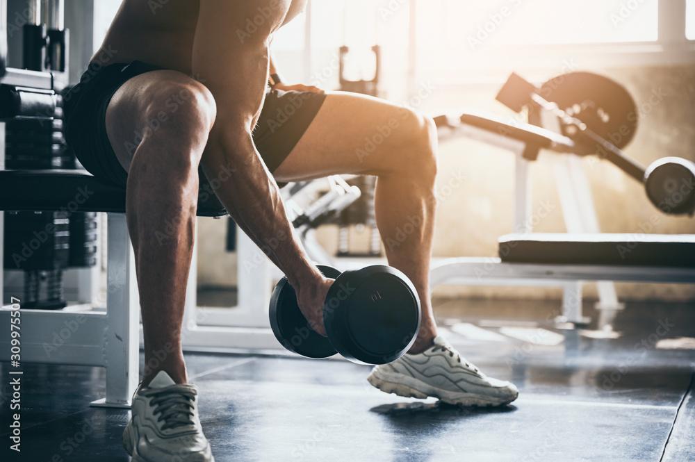 Fototapeta strong man exercising in the sport gym