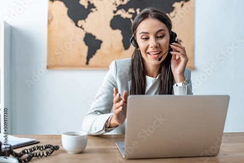 Tela attractive travel agent in headset working near laptop