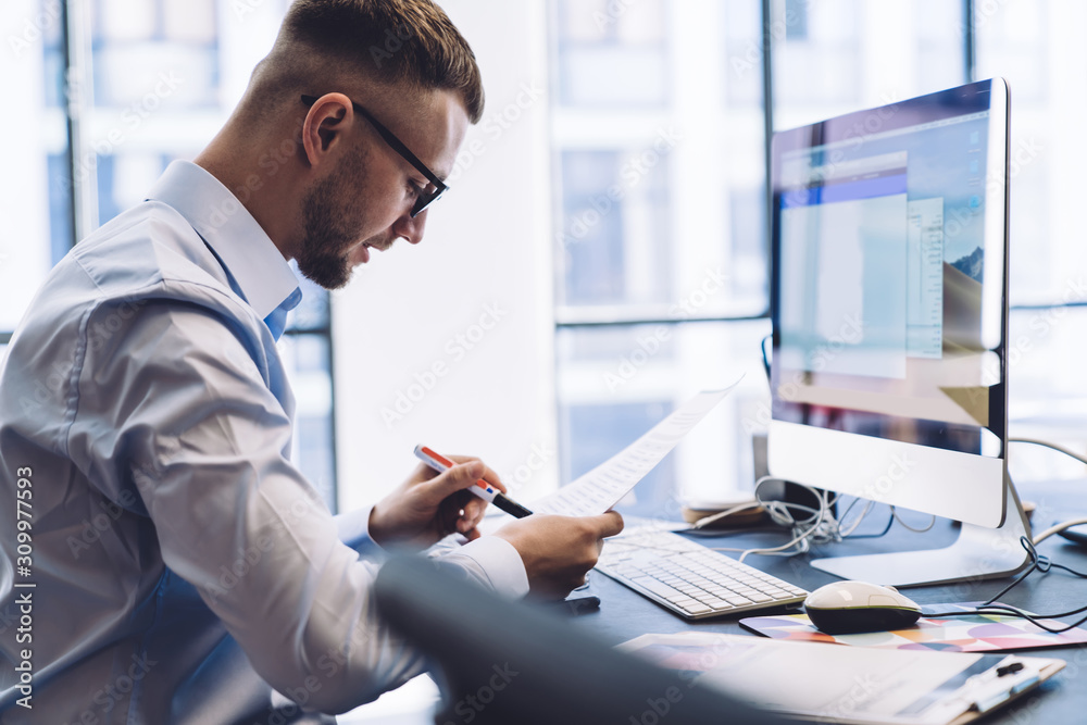 Fototapeta Serious manager checking document with pen at working table