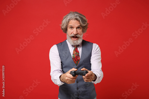 Amazed elderly gray-haired mustache bearded man in classic shirt vest and colorful tie isolated on red background in studio Wallpaper Mural
