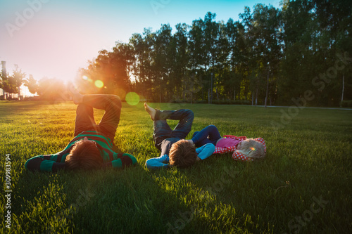 Fototapeta father with son and daughter relax on green grass at sunset obraz