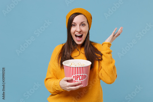 Excited young brunette woman girl in sweater and hat posing isolated on blue background Slika na platnu