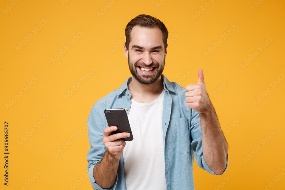 Fototapeta Smiling young man in casual blue shirt posing isolated on yellow orange wall background in studio. People lifestyle concept. Mock up copy space. Using mobile phone typing sms message showing thumb up.