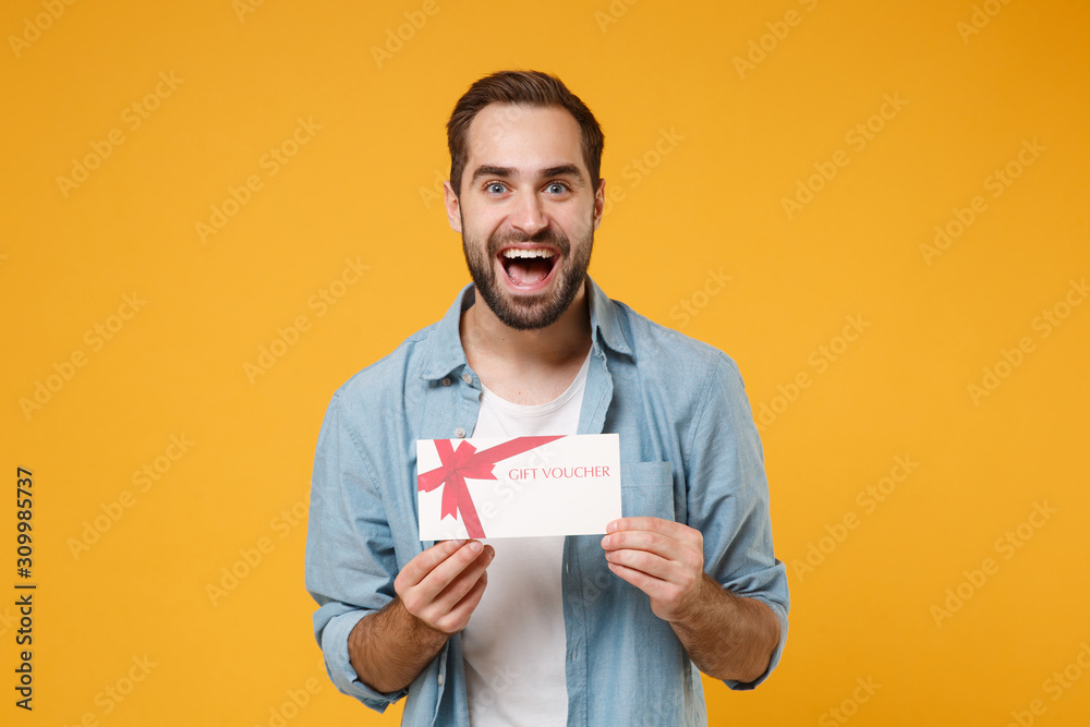 Fototapeta Excited young man in casual blue shirt posing isolated on yellow orange wall background, studio portrait. People lifestyle concept. Mock up copy space. Holding gift certificate, keeping mouth open.