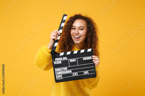 Cheerful young african american girl in fur sweater posing isolated on yellow orange background in studio Fototapet