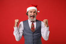 Joyful Elderly Gray-haired Mustache Bearded Santa Man In Christmas Hat Shirt Vest Tie Isolated On Red Background. Happy New Year 2020 Celebration Concept. Mock Up Copy Space. Doing Winner Gesture.