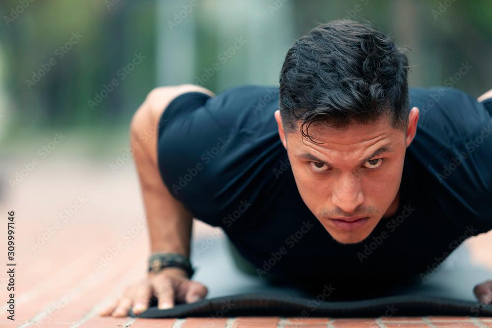 Fototapeta Young man exercising outdoors.