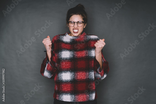 Angry young woman in glasses grinning with eyes closed and raised hands Canvas Print