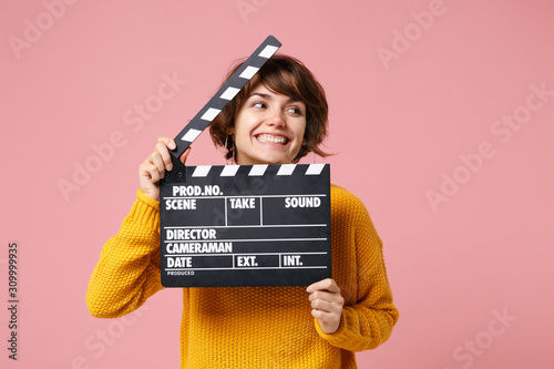 Fotografia Cheerful young brunette woman girl in yellow sweater posing isolated on pastel pink background in studio