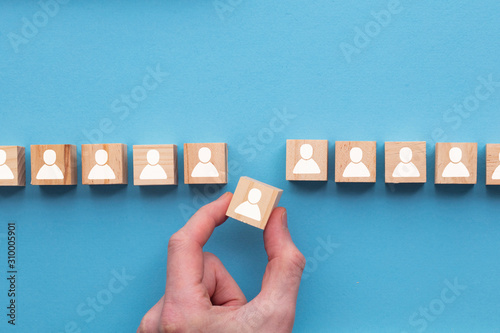 Hand choosing a wooden person block from a set Canvas Print