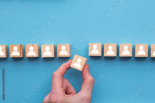 Obraz Hand choosing a wooden person block from a set. Employment choice concept - fototapety do salonu
