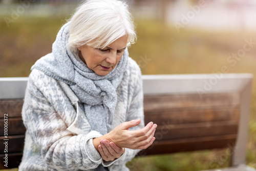 Senior woman with arthritis rubbing hands Wallpaper Mural