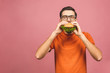 Leinwanddruck Bild - Young man holding a piece of hamburger. Student eats fast food. Burger is not helpful food. Very hungry guy. Diet concept. Isolated over pink background.