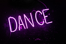 """Purple Neon Light Creating The Word """"DANCE"""" On A Black Wall In A Disco Or Night Club"""