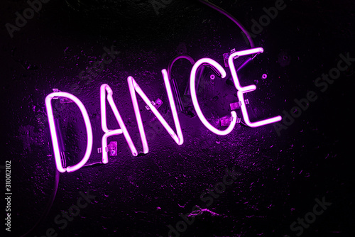 "Purple neon light creating the word ""DANCE"" on a black wall in a disco or night club"