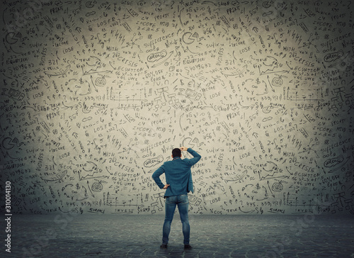 Rear view of puzzled businessman, hand to head thoughtful gesture, trying to solve hard mathematics calculations, formulas and equations Wallpaper Mural