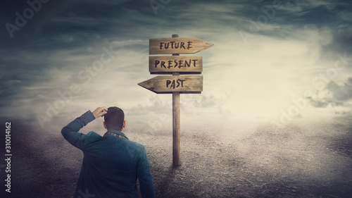 Surreal scene, businessman and a signpost arrows showing three different options, past, present and future course Fototapet