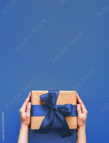 Valokuva Female hands hold gift box on deep blue background with copy space for design