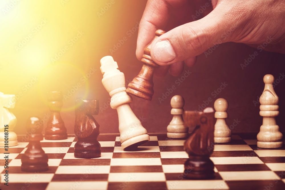 Fototapeta Human hand playing chess, buisness strategy concept