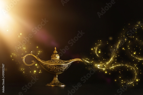 Foto Image of magical mysterious aladdin lamp with glitter sparkle smoke over black background